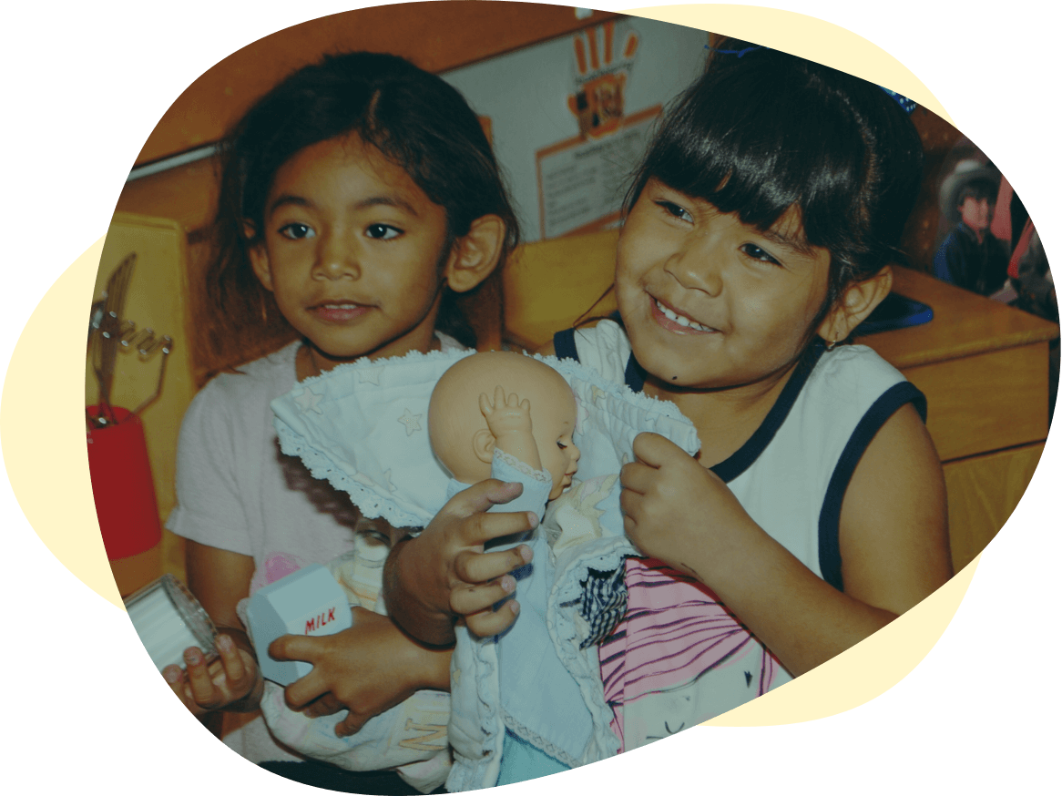 Two children sitting in a classroom smiling and holding up a baby doll.