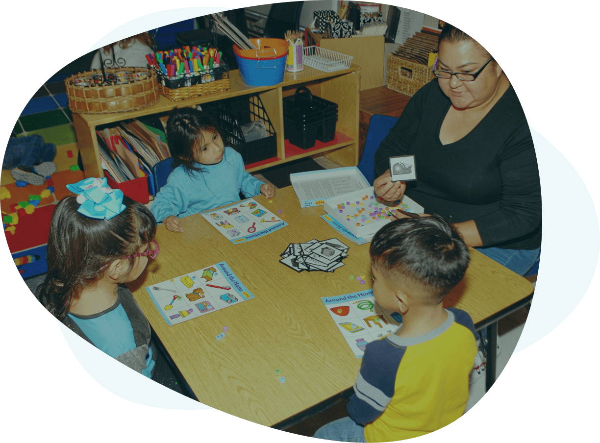 A teach and three students learn around a table in a classroom.