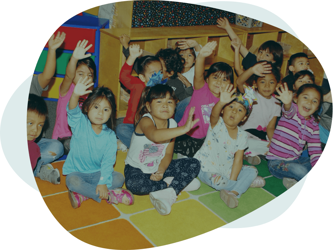 Many students sit on the classroom floor and raise their hands